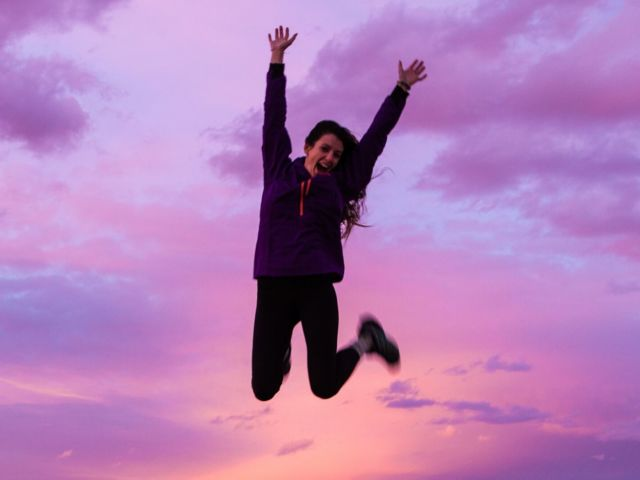 woman jumping in pink clouds