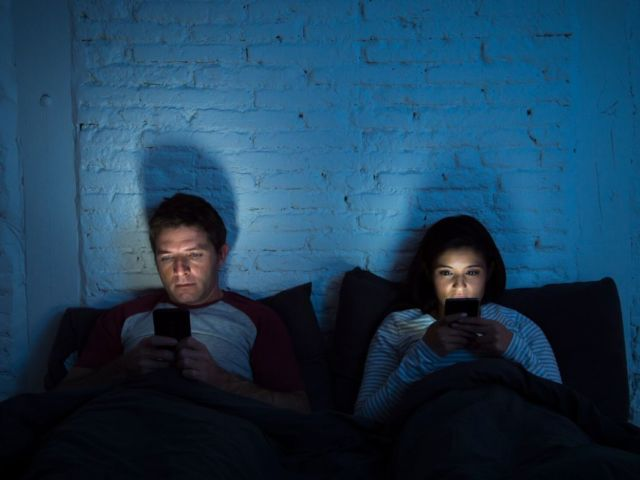 couple in the dark on cell phones communicating